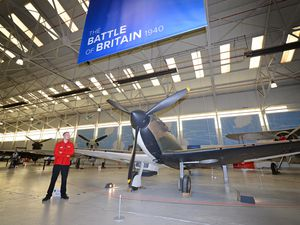 Visitor experience assistant Dominic Newton next to a spitfire which features in the new exhibition to commemorate the Battle of Britain on its 80th anniversary