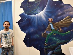 Mural artist Rory McCann with the Big Friendly Giant mural he hand painted in the pre-operative area