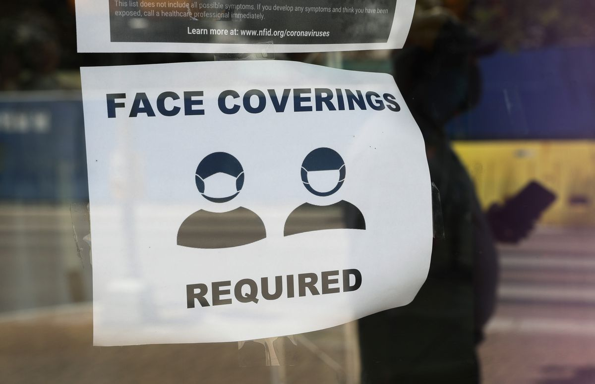 A visitor wearing a mask to protect against the spread of COVID-19 passes a sign requiring masks