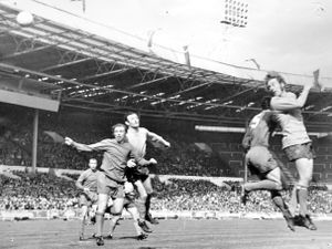 Joey Owen rises to get in a header as he beats Tony Newcombe to the ball. Jimmy Murray is also on hand with Bill Carter in close attendance.