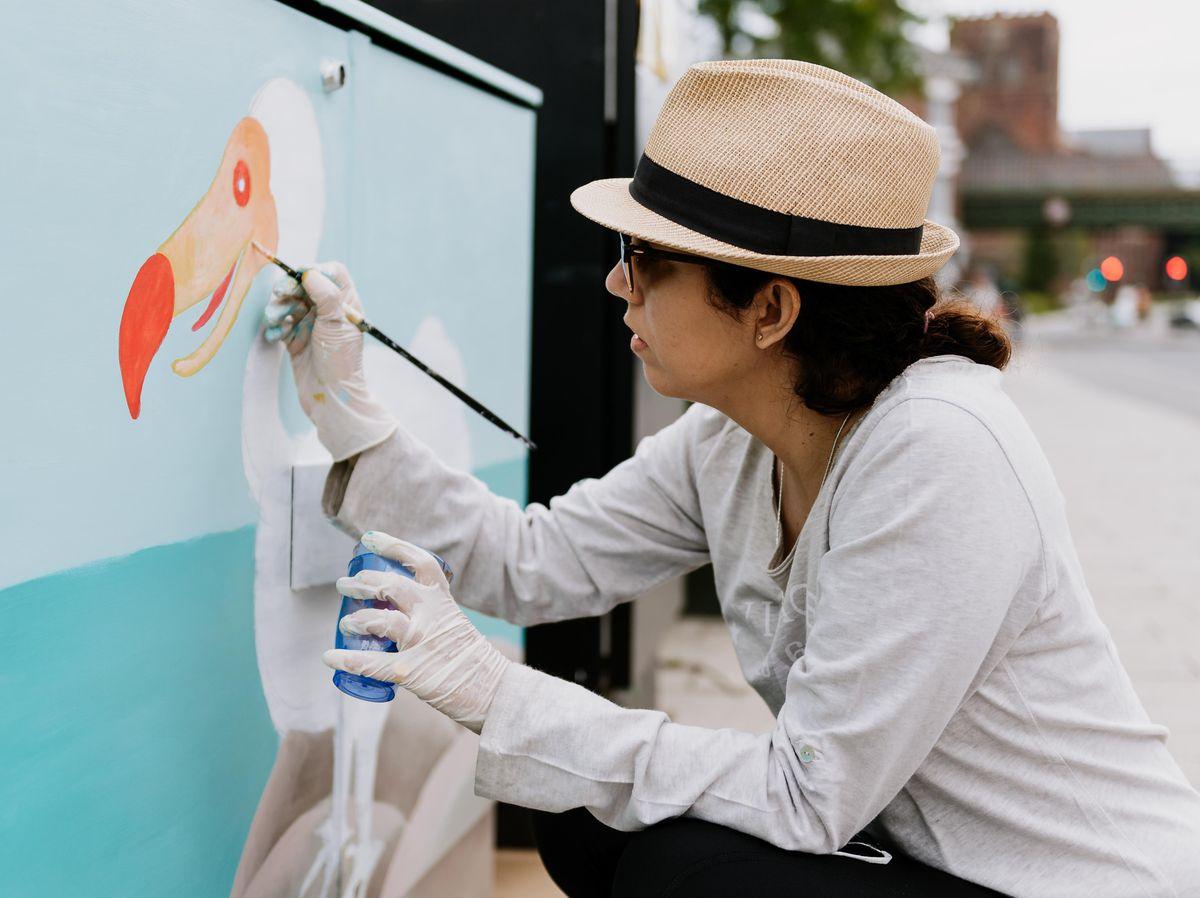 Gisela Robinson paints one of the BT boxes near English Bridge in Shrewsbury