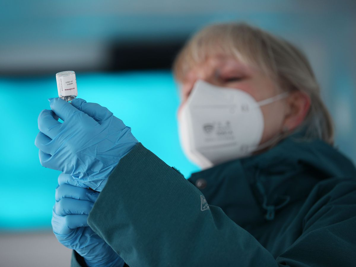 An NHS nurse prepares a dose of the Oxford-AstraZeneca Covid-19 vaccine in a modified bus, in the car park of the University of Greenwich, London (Yui Mok/PA)