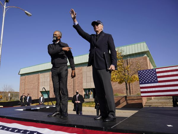Democratic presidential candidate Joe Biden and former President Barack Obama greet each other at a rally in Flint