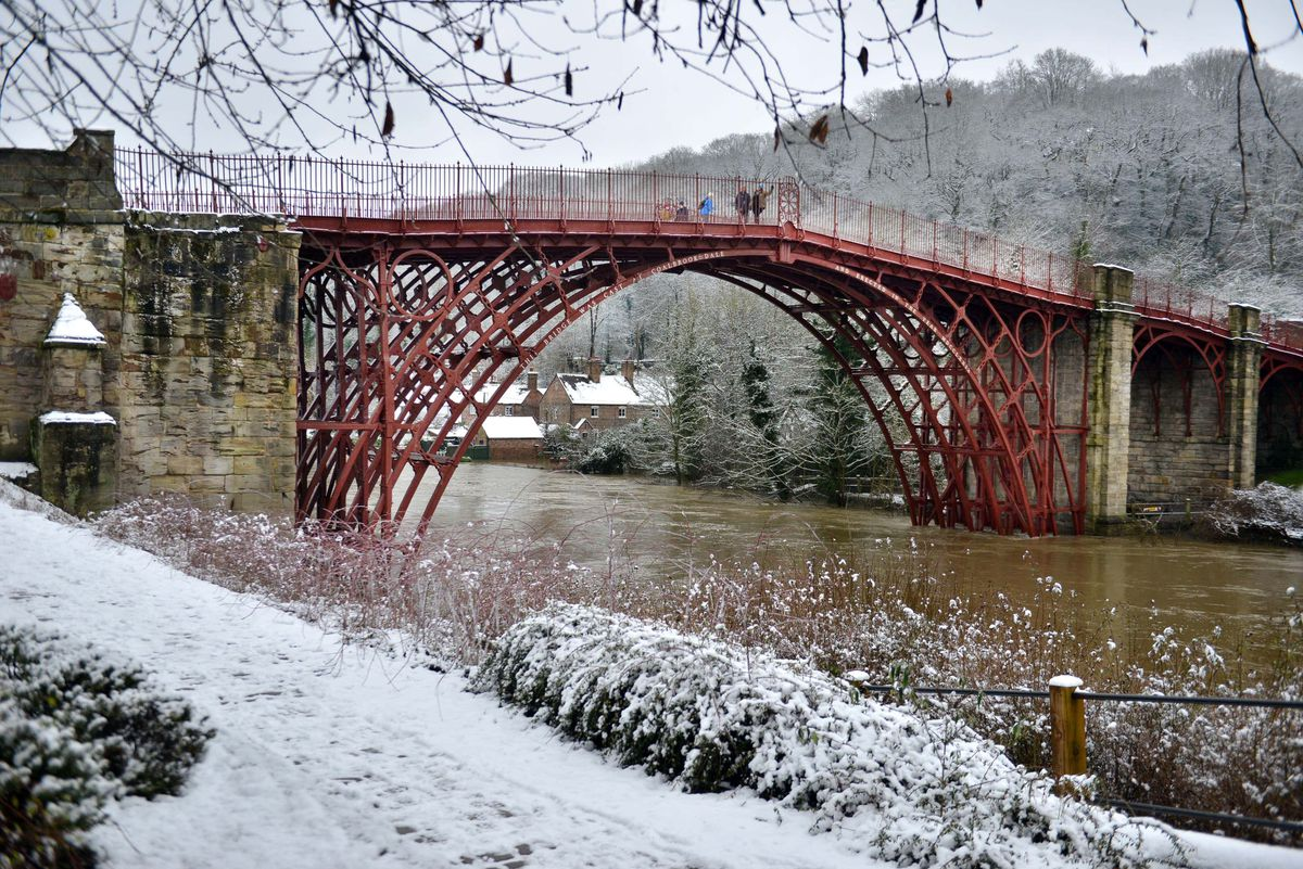 Snow in Ironbridge, where the River Severn remained high on Sunday