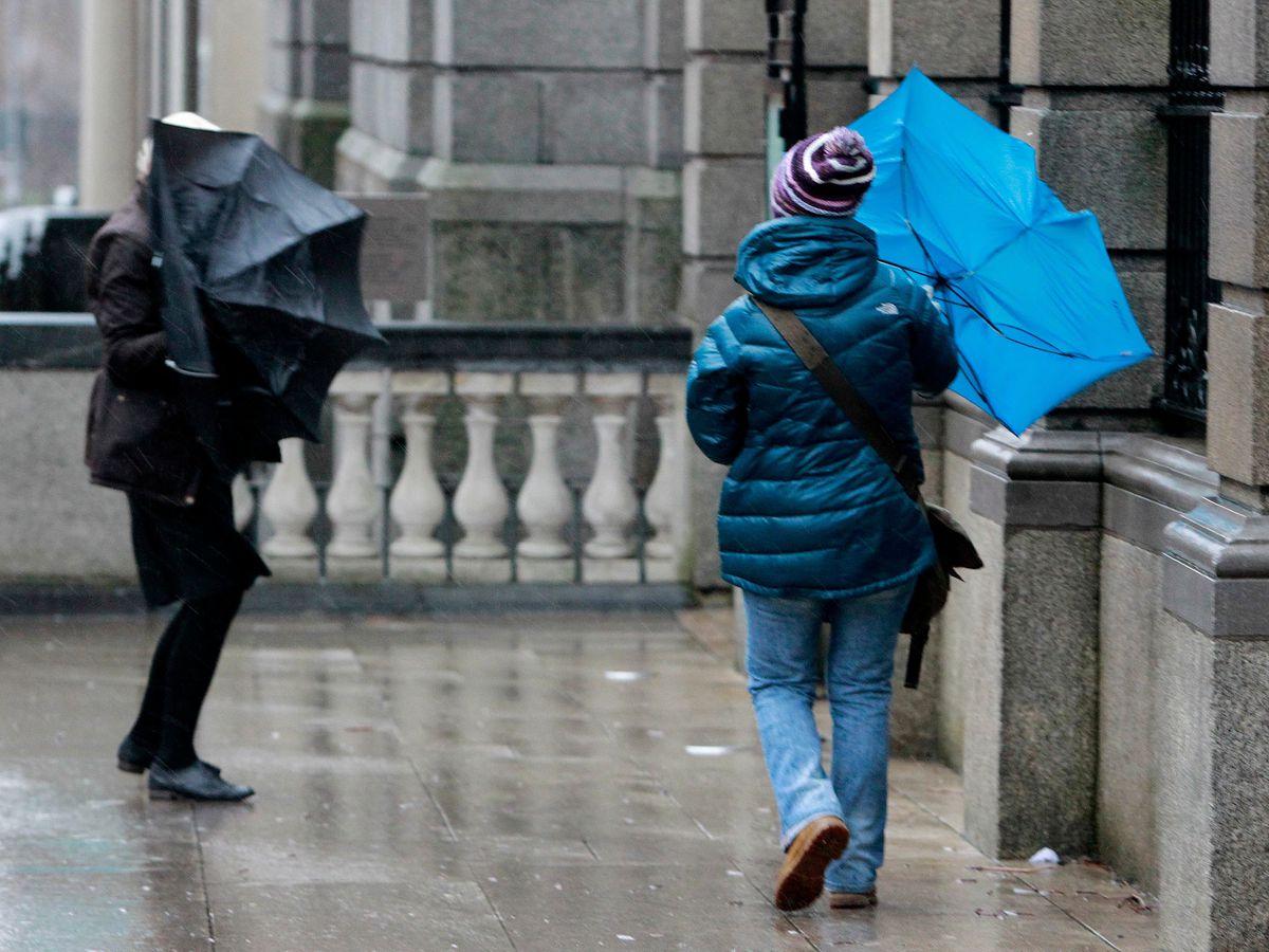 People struggle to keep their umbrellas up