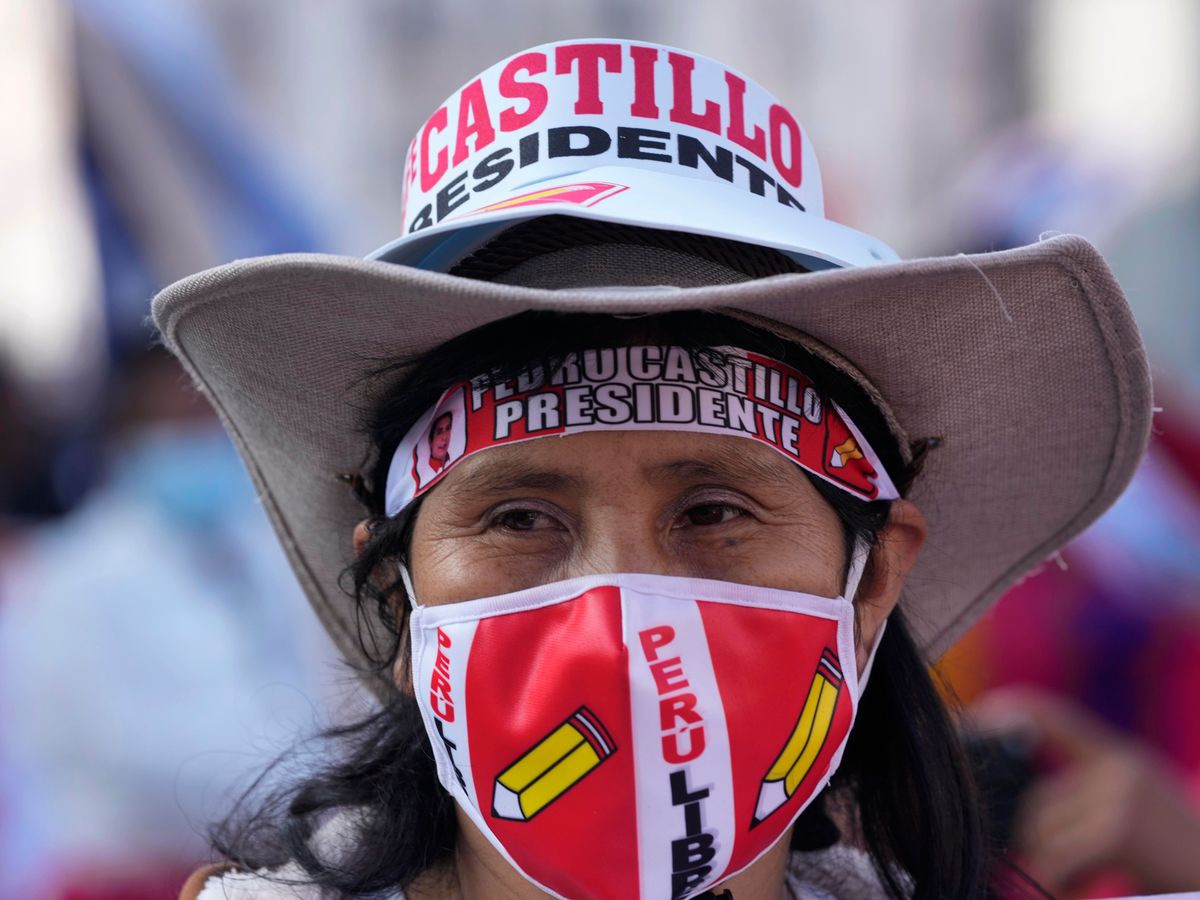 A woman in a wide-brimmed hat joins a march in support of presidential candidate Pedro Castillo
