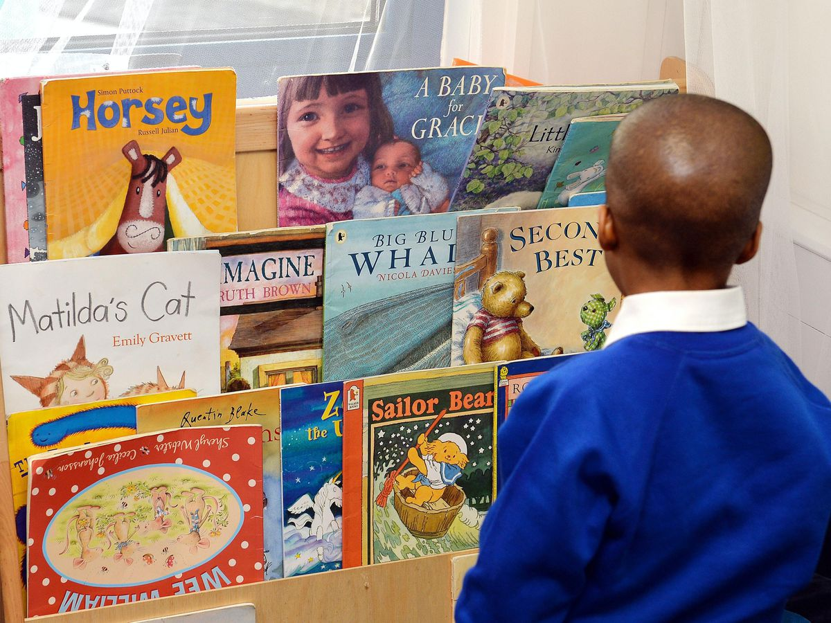 A child looking at books in a nursery