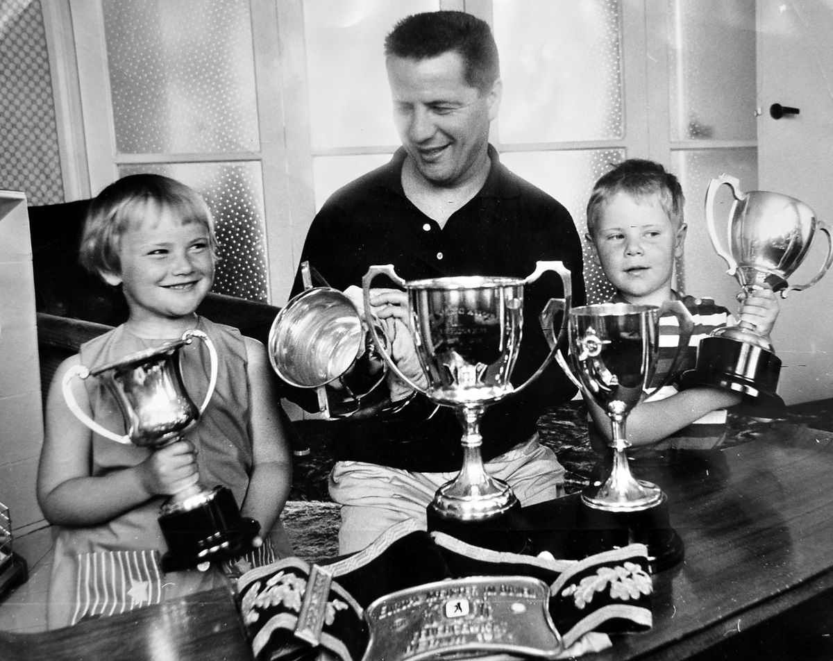 Giving his many trophies a polish in 1966 with children Carol and Mark.