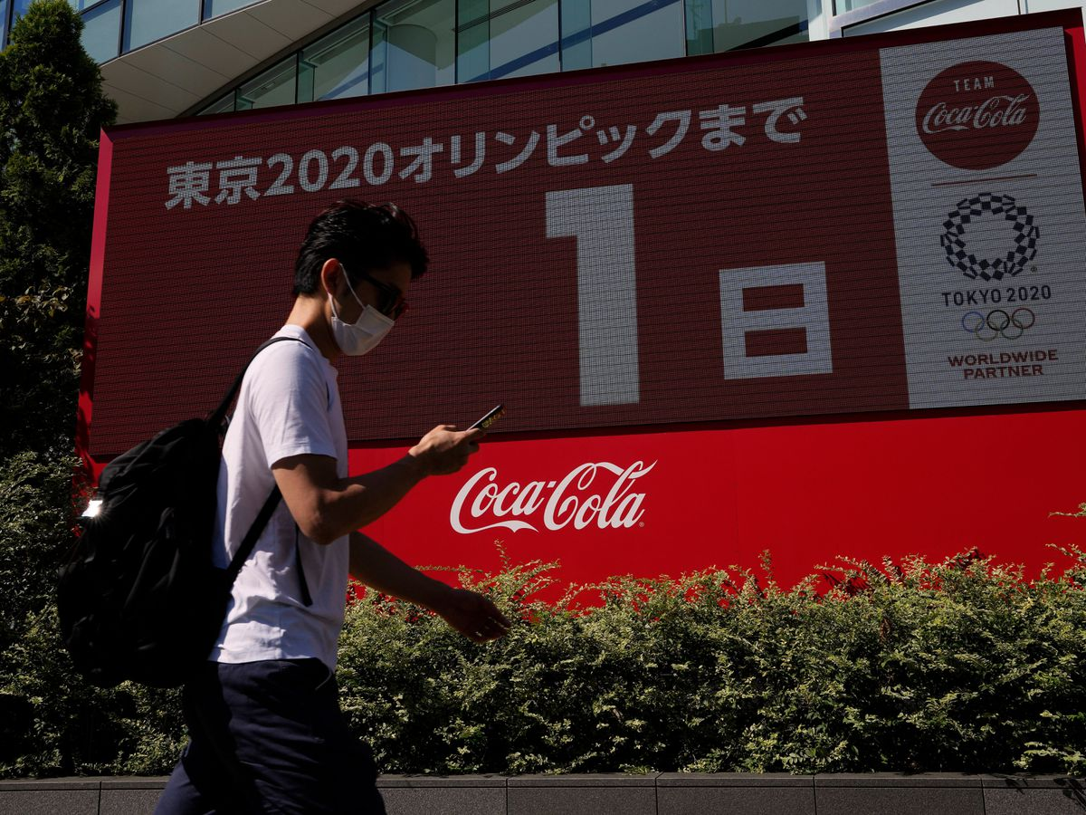A pedestrian passes by a large electronic display shows one day until the opening ceremony of 2020 Tokyo Olympics
