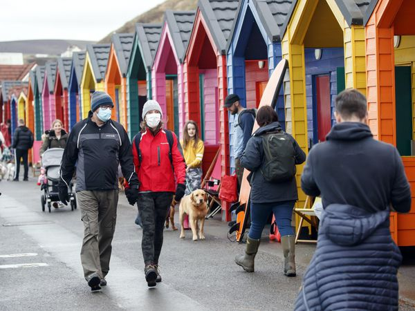 People wear face masks as they walk past beach huts in Saltburn-by-the-Sea.