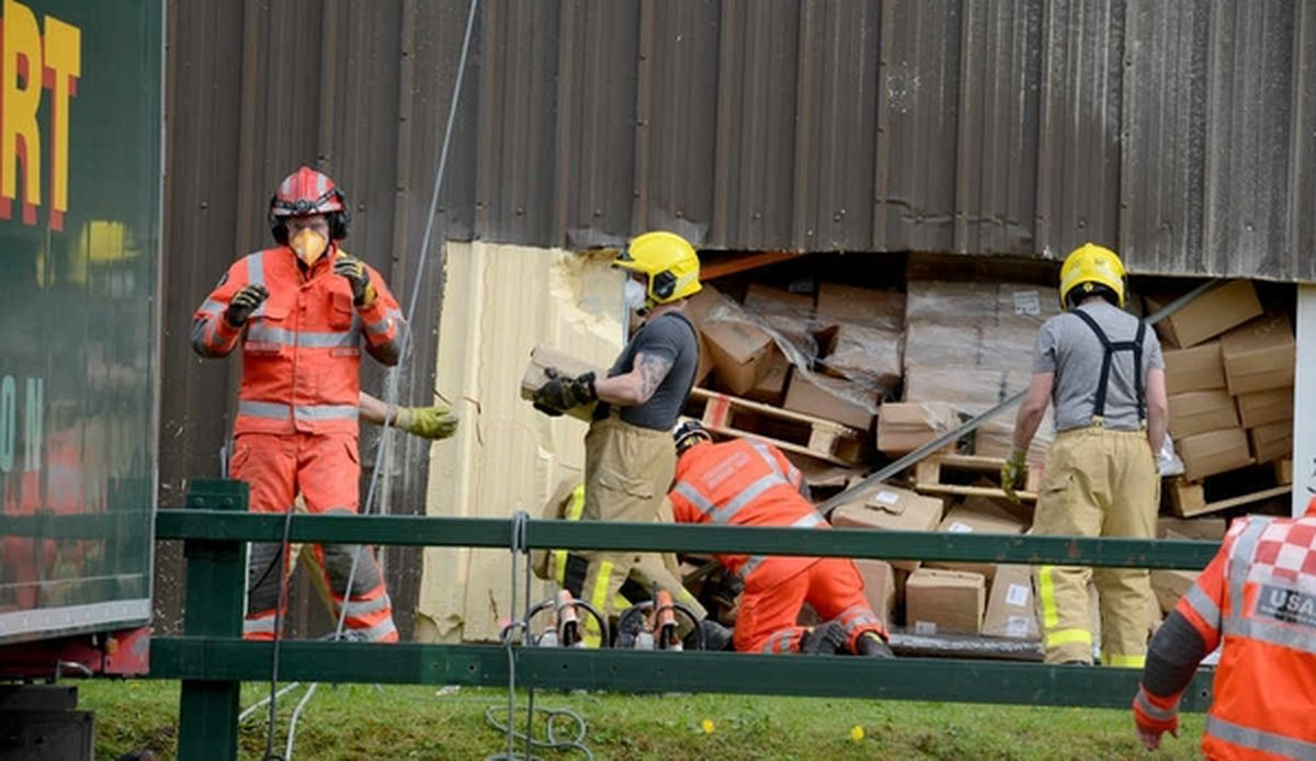 Fire crews clear a path to the trapped man through a hole cut in the wall