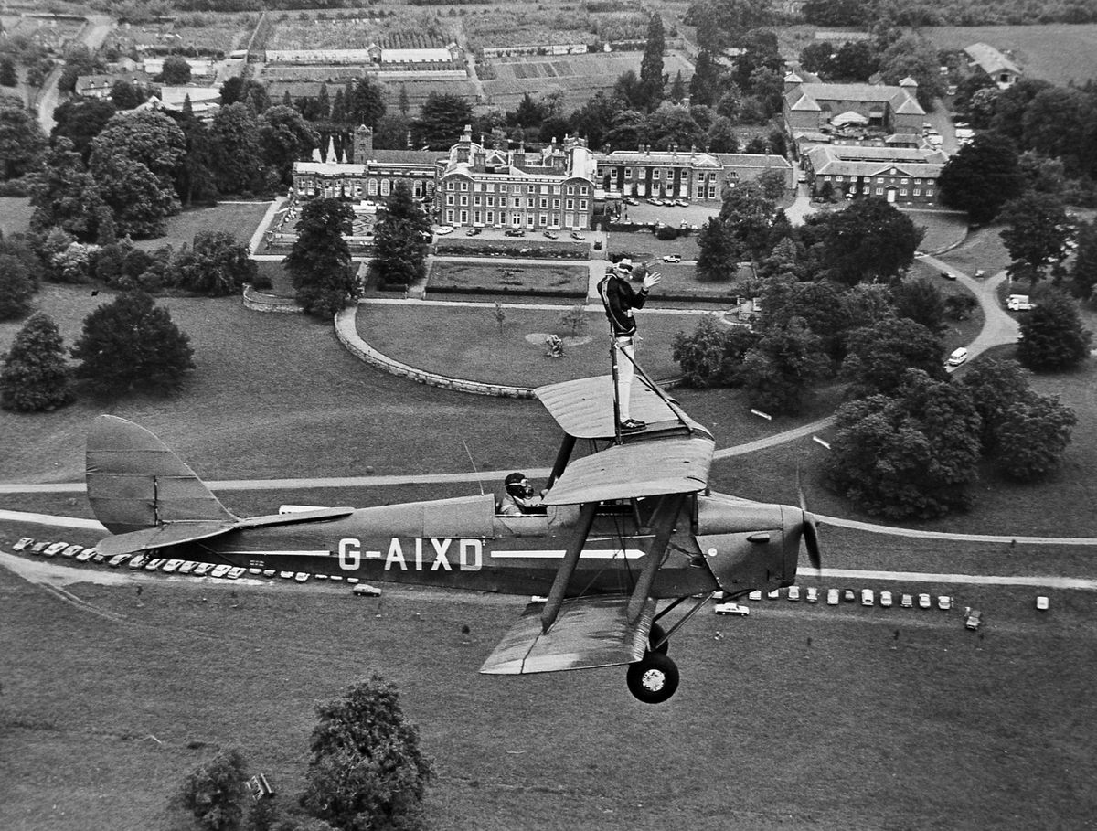 A Tiger Moth biplane above Weston Park on July 14, 1986, with one passenger who was not properly strapped in. He was wing walker Iain Shorthouse on a practice flight in advance of Weston Park's 14th annual air display which was expected to attract over 10,000 people.
