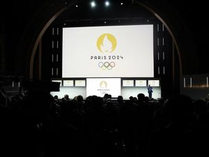 Paris 2024 Olympic logo is displayed on a screen