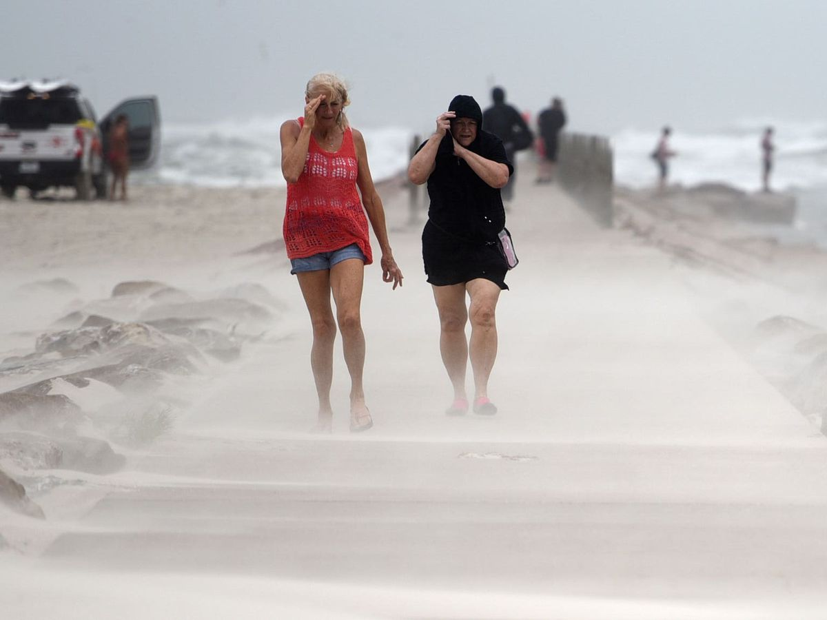 People in Texas shield their faces from wind and sand ahead of Hurricane Nicholas