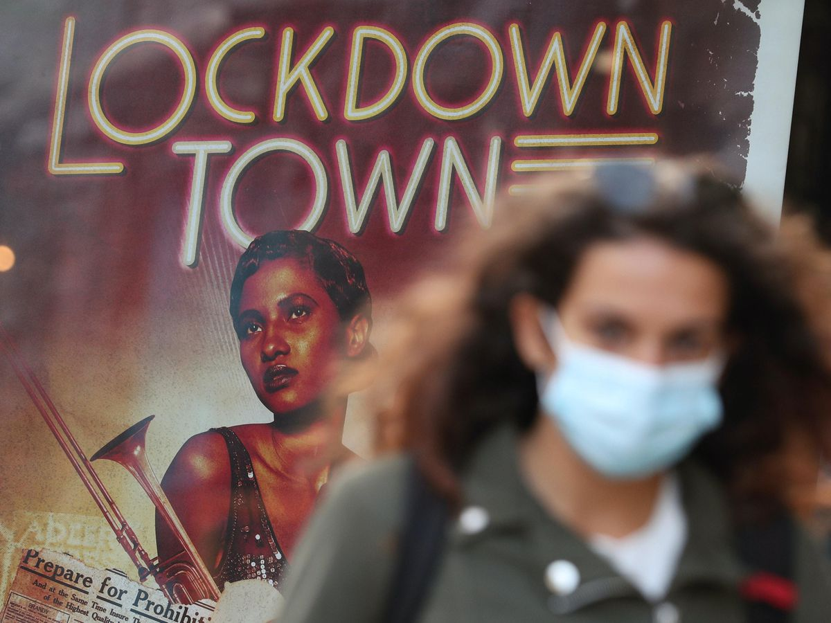 A woman wearing a face mask walks past a poster advertising the music event Lockdown Town