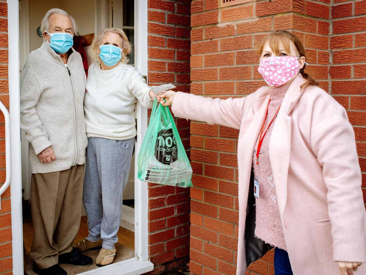 Volunteer Kim Wootton helps out residents John and Joyce Hinton with shopping deliveries