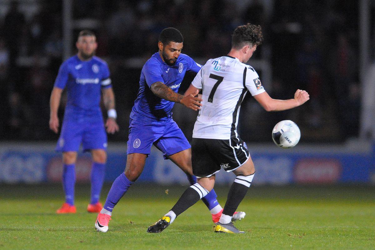 Ellis Deeney of Telford battles for the ball with Tom Owen-Evans