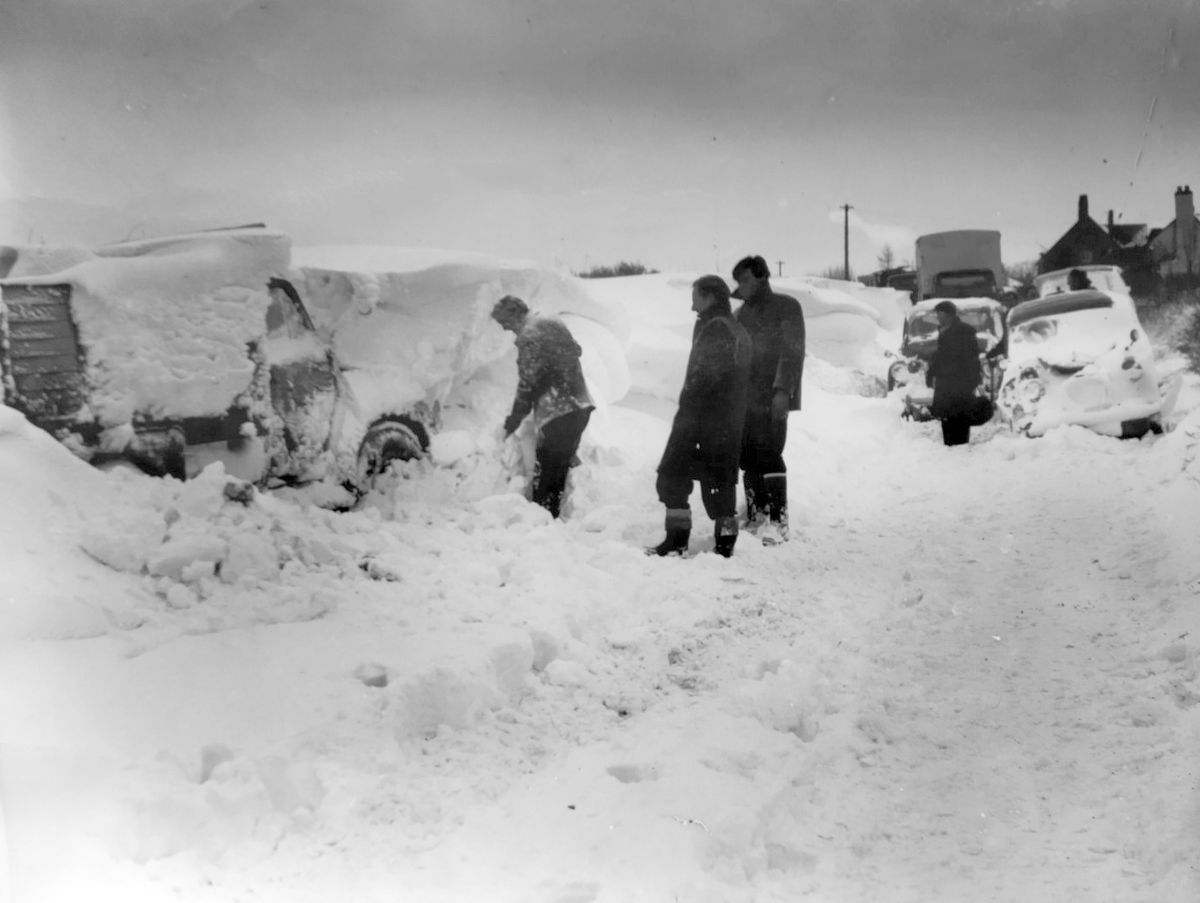 """nostalgia pic. Wellington. nostalgia pic. Arleston. A car being dug out of heavy snow in April 1961. This picture was emailed in by David Thorp u534gold@gmail.com: """"I took it in April 1961 at Hilltop Garage, where I was forced to spend the night.  I was on my way home to Little Dawley when I got stuck. Hilltop garage is on Dawley Road, Wellington, about four hundred yards on the left from the A5 traffic lights (Cock Inn). In those days it was a Repair garage (I believe they sell cars there now). I cannot for the life of me remember the name of the chap who ran the garage, but he was a good friend at the time. I  was working for BIP Chemicals (Birmingham) and was driving an Austin 1100 .  I managed to get up the hill as far as the Garage, and pulled into his yard.  I had snow chains on the car as it was front wheel drive (useless in snow) . Rear wheel drive is better because you can put a load of weight in the boot and then with front to rear weight transfer you have traction.  Best car in snow used to be the Beetle - rear engine.  I spent some time in the workshop but eventually when (Dave?) went to his bed I retired to the car where I kept the engine running on and off most of the night to keep the heater going after covering the radiator with a sack... I live at 17 Moorhouse Close, Wellington TF1 2BF 01952 251504"""". Wintry weather. Snowy weather. Winter scene. Winter scenes. Library code: Wellington nostalgia 2021. Arleston nostalgia 2021. .."""