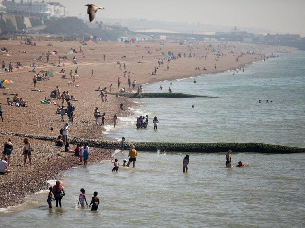 People enjoying the sun on Brighton beach as the UK basks in the late summer heat (Steve Paston/PA)