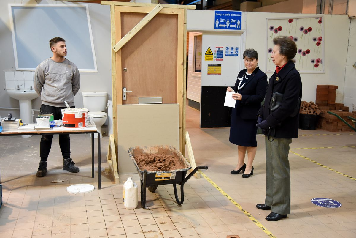 Joe Jones, trainee with The Wrekin Housing Trust, shows off his tiling skills to the royal visitor