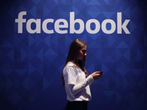 A woman using her phone under a logo of Facebook