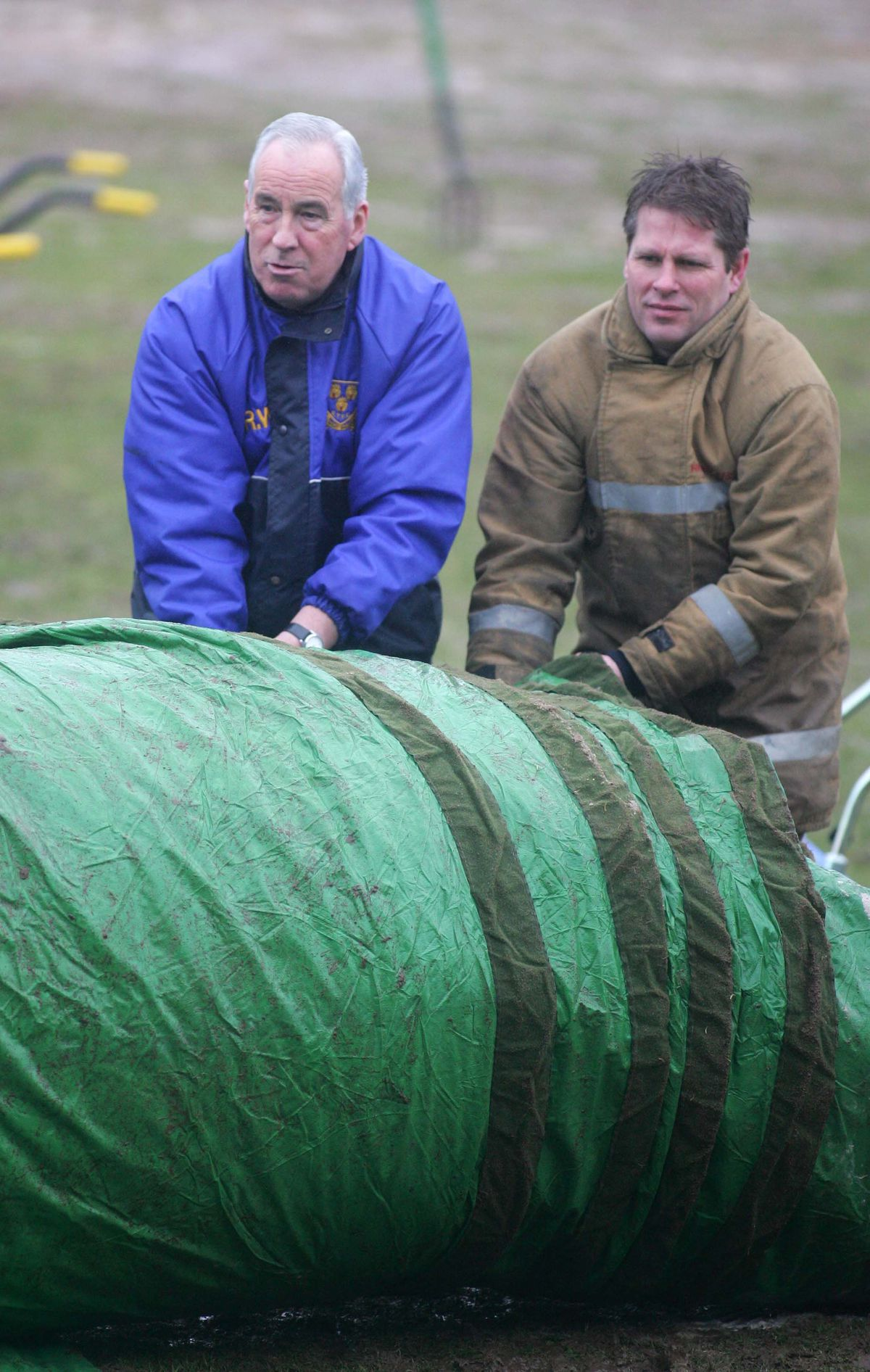 Roland Wycherley helps the fire brigade to roll up the pitch covers