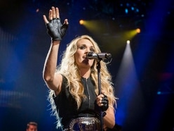 Carrie Underwood cradles growing baby bump at CMA Awards