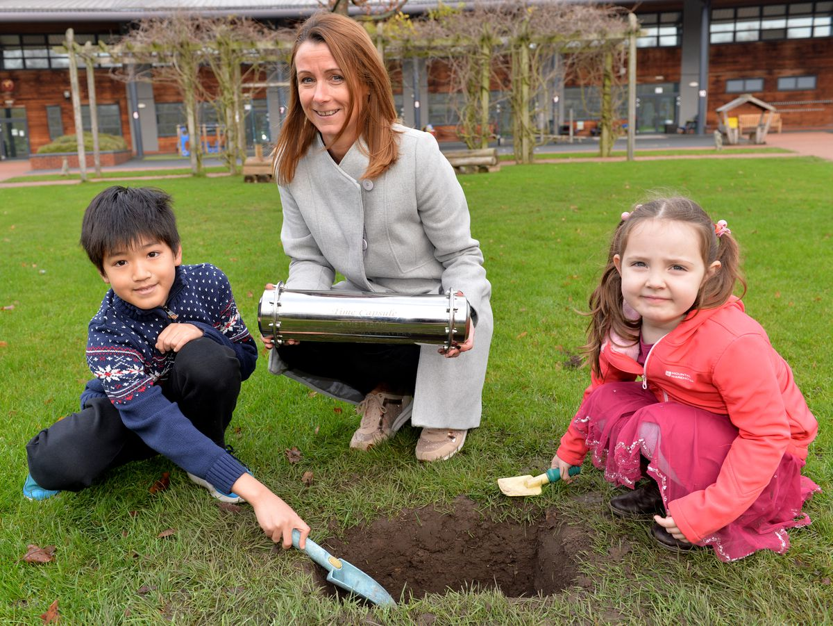Teacher Helen Grant with students and the time capsule