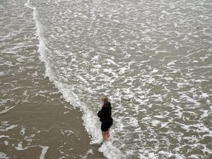 Woman paddles in sea