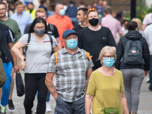 People wearing face masks among crowds of pedestrians in London