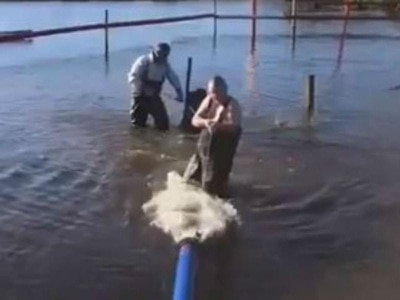 Minister hailed for wading into flood water to help fix pump