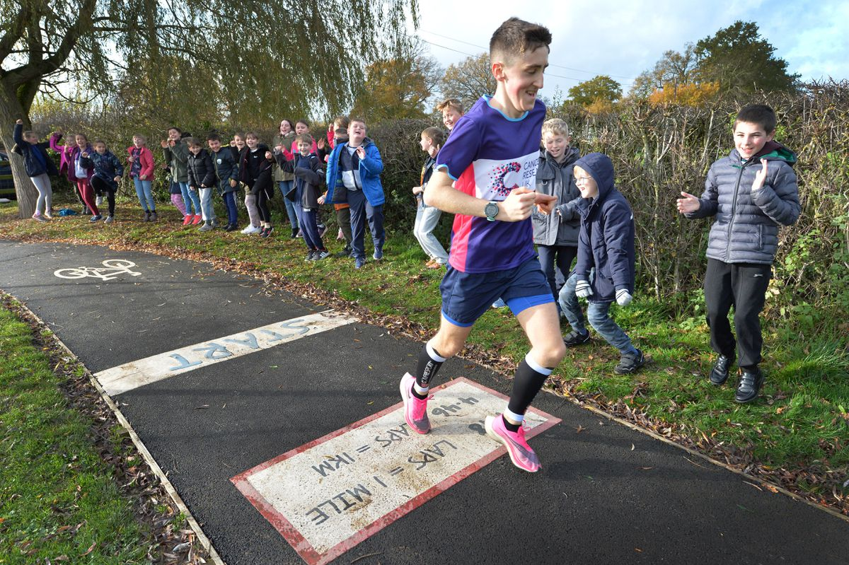 . Jack Pickett, running 187 laps of Criftins Primary School running track cheered on by his brother ,Tom , right, and other pupils at the school