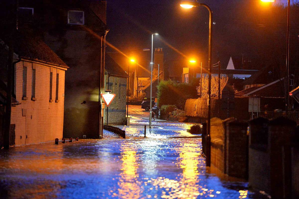 Water flows into Weeping Cross Lane in Ludlow on Sunday evening