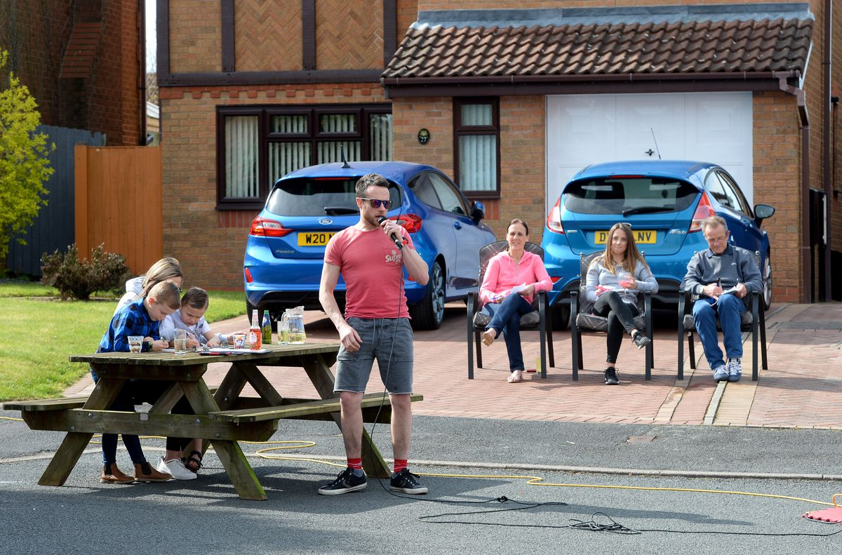 Residents sit in their driveways for a game of bingo