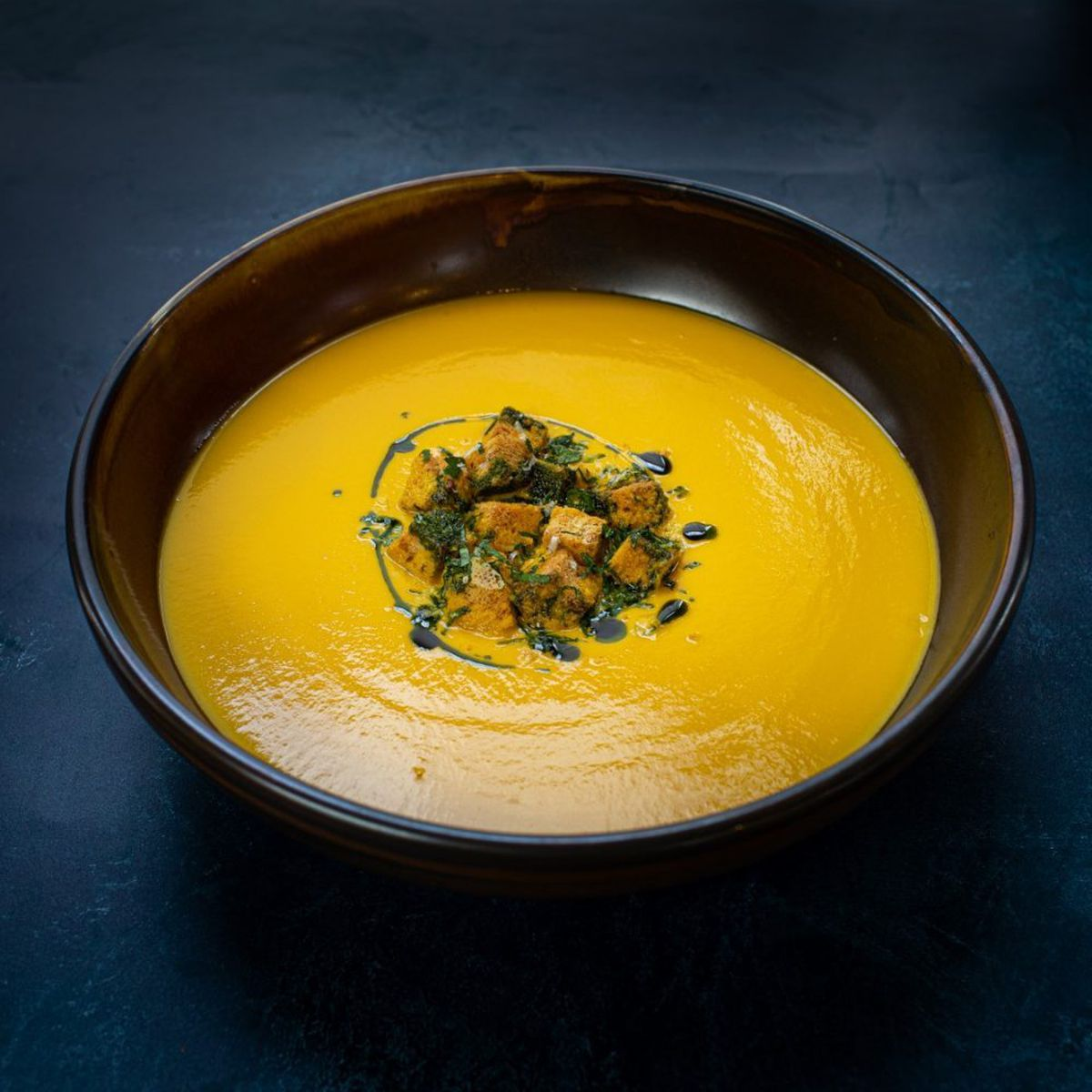 Carrot and ginger soup with parmesan croutons and pasley