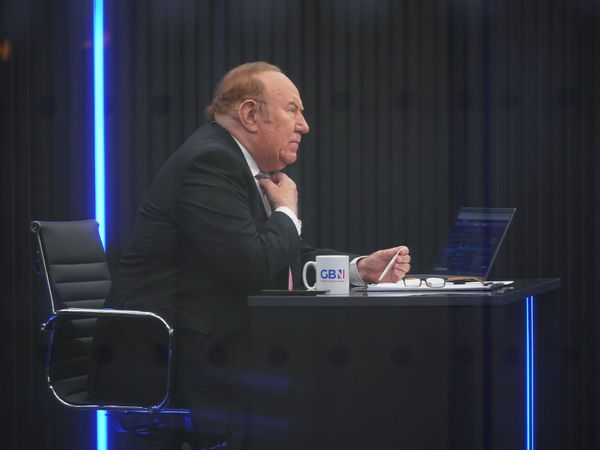 Andrew Neil sits at a desk