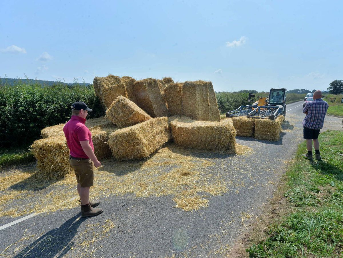 BORDER COPYRIGHT SHROPSHIRE STAR STEVE LEATH 22/07/2021..Pic along the road to Ludlow (The road that cuts right through the middle of the Ludlow Race Track, where a farmer has had a mishap, temporarily blocking the road after tipping his hay load over. Nobody was injured and party involved didnt want to give a contact number..