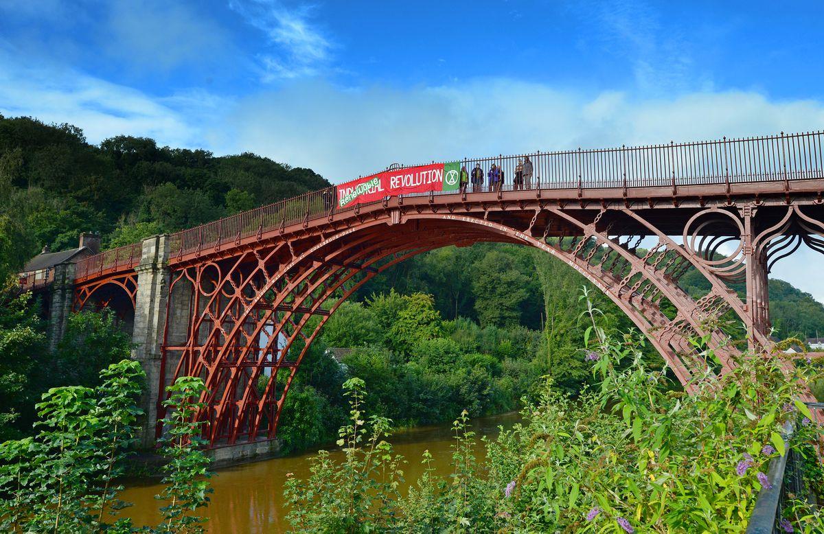 Climate change protestors tie a banner onto the Iron Bridge, in Ironbridge