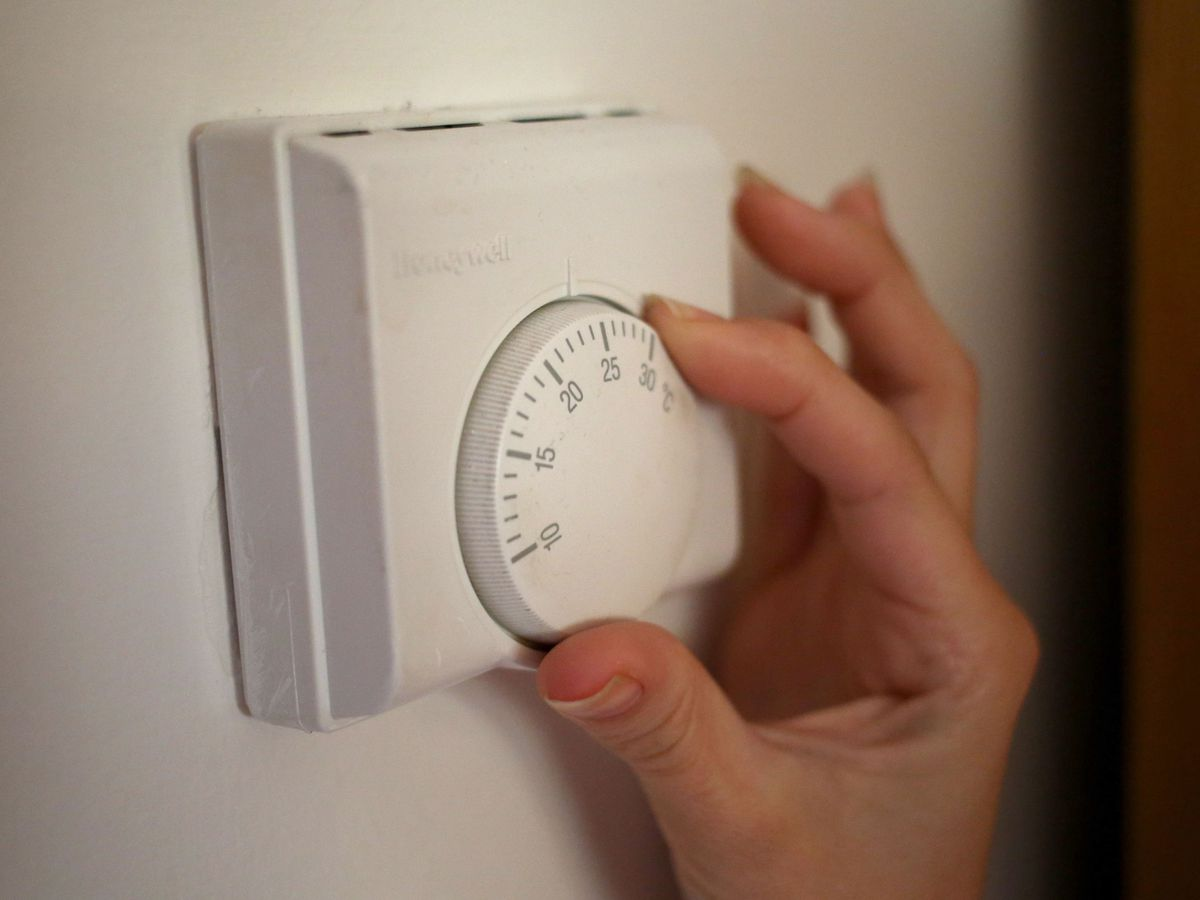A woman adjusts a central heating thermostat