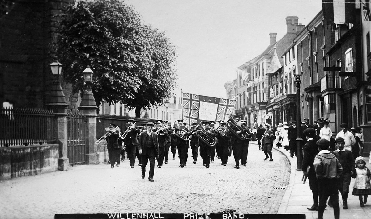 """Here come Willenhall Prize Band on parade in Newport in July 1909, and following them is Newport District Juvenile Oddfellows – we know that because it says so on the flag. This is a postcard from the collection of the late Malcolm Miles of Newport, and loaned by his widow Sue. The message on the back was: """"Dear A, We arrived home quite safe at 10.15pm. I am sending you the photo as promised."""" It was addressed to Mrs Fellows, of Gorsty Bank, Shifnal."""