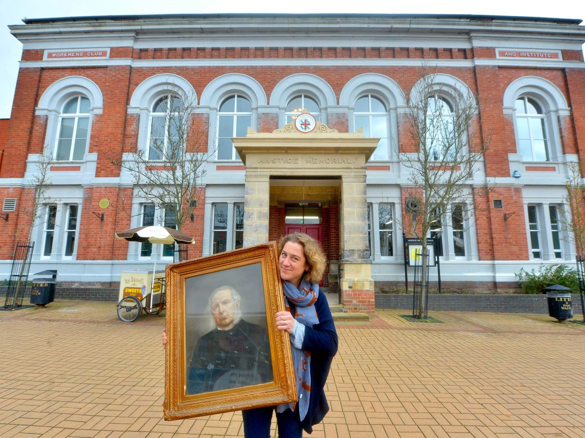 Gemma Aston outside The Anstice with a picture of John Anstice, who the building it named after