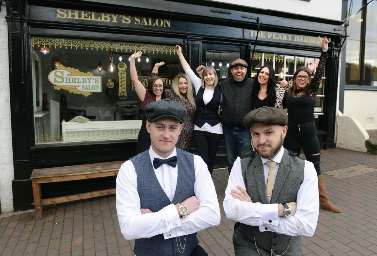 Martin Curry, left and Neil Reynolds of the Peaky Barbers pictured with staff outside the shop