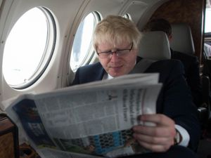 Boris Johnson reads a newspaper while sitting by a window on a plane