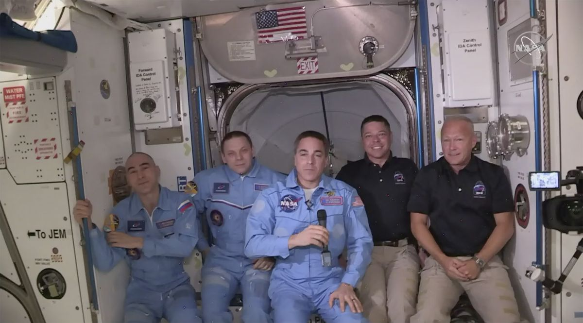 This photo provided by NASA shows Bob Behnken and Doug Hurley, far right, joining the the crew at the International Space Station, after the SpaceX Dragon capsule pulled up to the station and docked Sunday, May 31, 2020