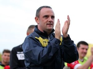 Chris Hughes the manager of Newtown AFC applauds the home supporters at the end of the game .