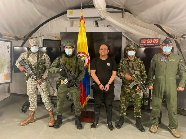 """One of Colombia's most wanted drug traffickers, Dairo Antonio Usuga, alias """"Otoniel,"""" leader of the violent Clan del Golfo cartel, is presented to the media while flanked by armed soldiers at a military base in Necocli"""