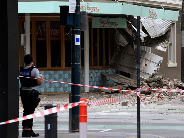 A police officer closes an intersection where debris is scattered in the road after an earthquake damaged a building in Melbourne