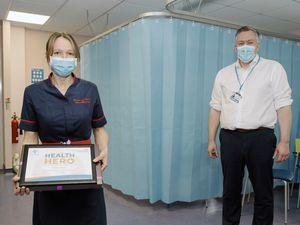 Rebecca Warren, clinical lead nurse for the RJAH hospital hub, receiving her health hero award from Mark Brandreth, chief executive