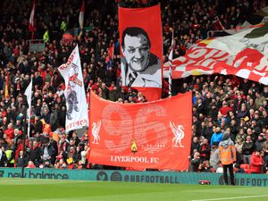 A banner adorned with the number 96 is waved at Anfield