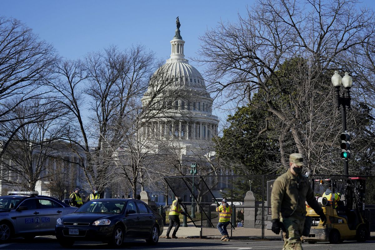 With the U.S. Capitol in the background, workers place fencing around the Capitol grounds the day after violent protesters loyal to President Donald Trump stormed the U.S. Congress in Washington, Thursday, Jan. 7, 2021. (AP Photo/Evan Vucci).